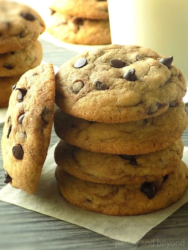 Stacked chocolate chip cookies on a parchment paper that is on a gray surface.