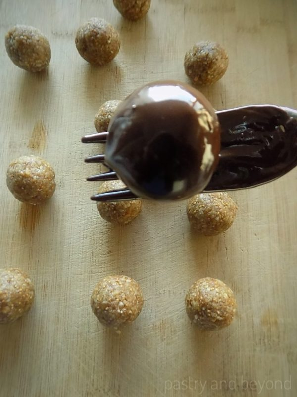 Steps of Making Healthy Fig and Walnut Balls: Dipping the balls into melted chocolate