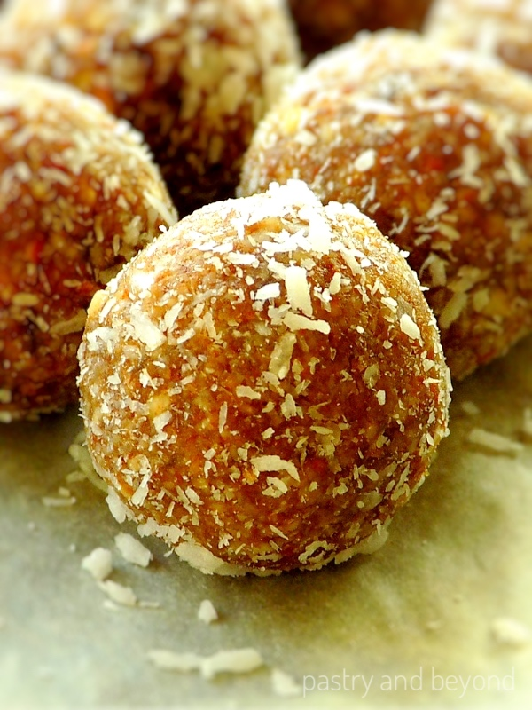 Almond date balls covered with shredded coconut on a white surface.
