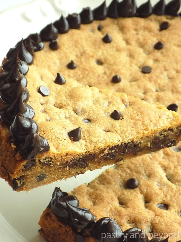 Chocolate chip cookie cake slice decorated with chocolate ganache on a cake plate.