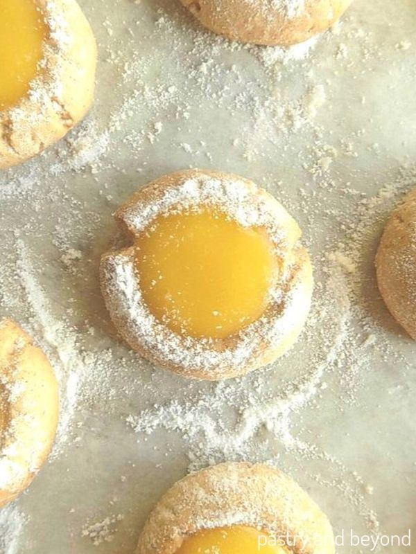 Lemon curd thumbprint cookies on a parchment paper.