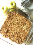 Overhead view of apple crumble in a baking dish with apples, plates, forks in the background.