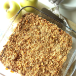 Easy apple crumble is on a baking dish and golden apples, plates, forks are on the back.