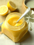 Homemade lemon curd in a jar with a spoon, half lemons in the background.