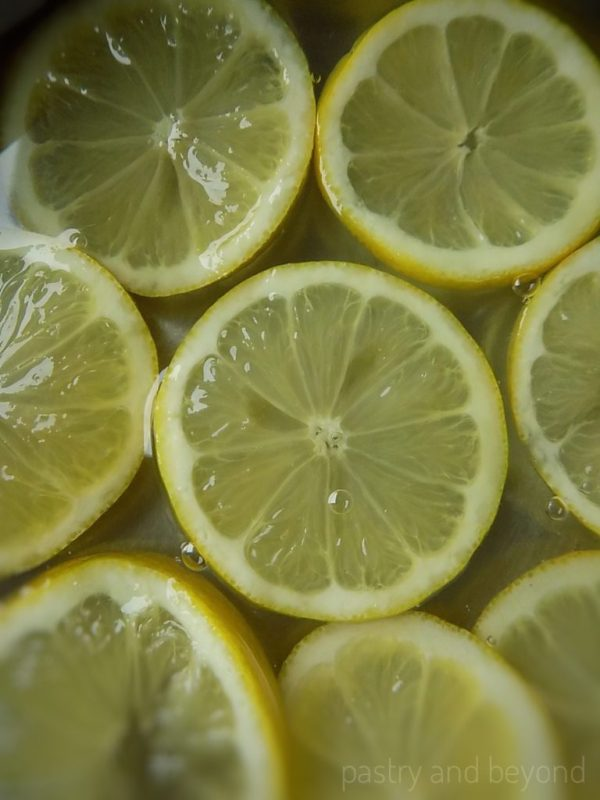 Steps of Making Candied Lemons: Adding the lemon slices into the syrup.