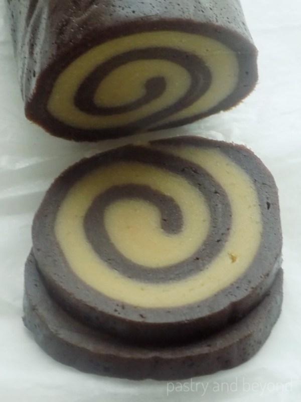 Unbaked swirl cookie slices.