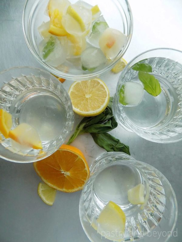 Fancy ice cubes with lemon, orange and basil leaves in glasses.