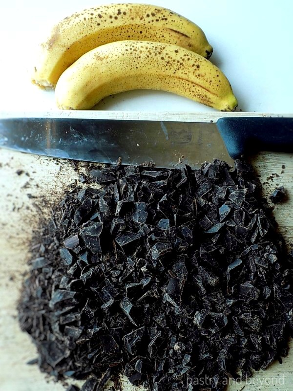 Bananas on a white surface, chopped chocolate on a chopping board with a sharp knife.