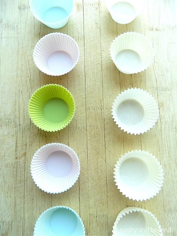 Green, pink, blue silicone mini cupcake liners and white paper cupcake liners on a wooden surface.