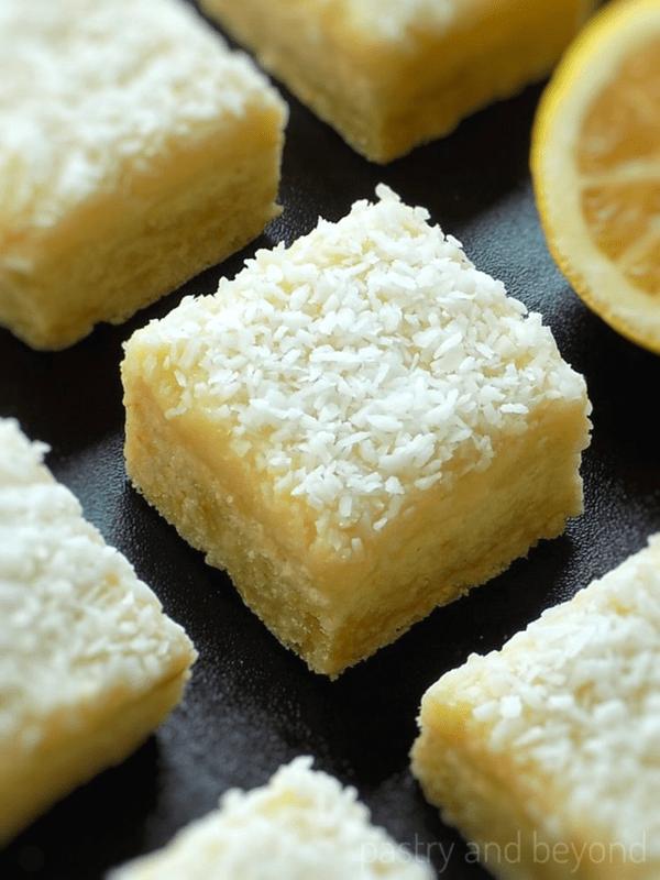 Lemon Coconut Bars on a black surface.