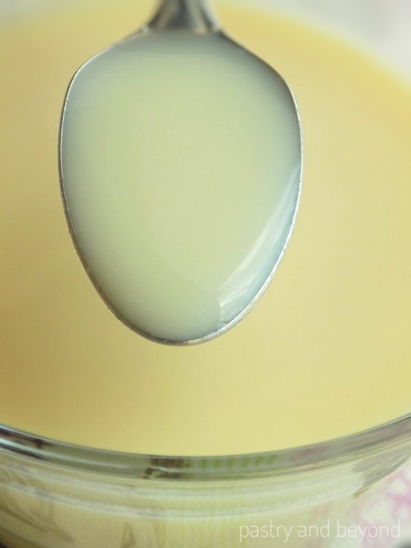Showing the consistency of homemade condensed milk with a spoon.