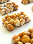 Candied hazelnuts on a white surface.