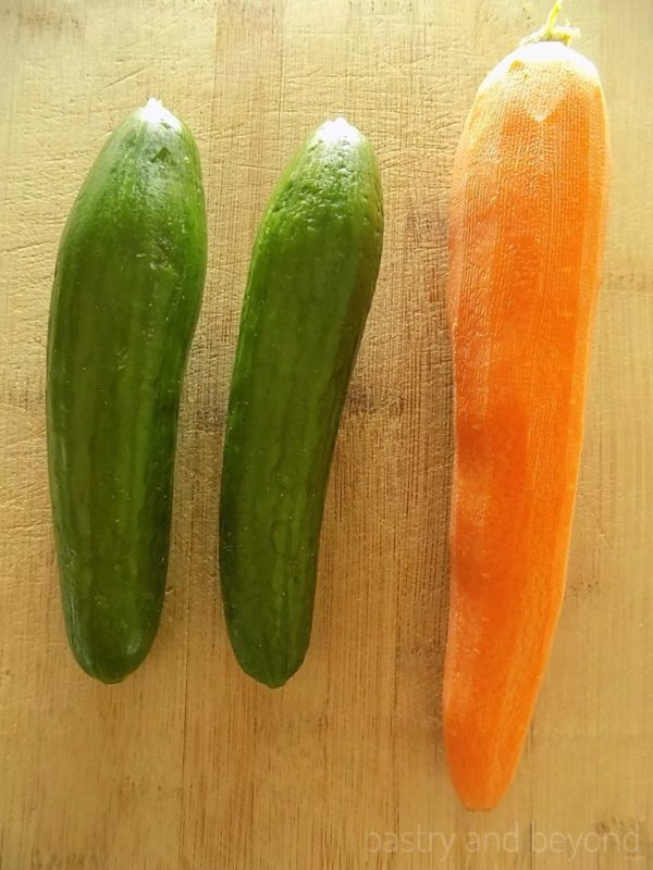 Two medium cucumbers and a large carrot on a chopping board.