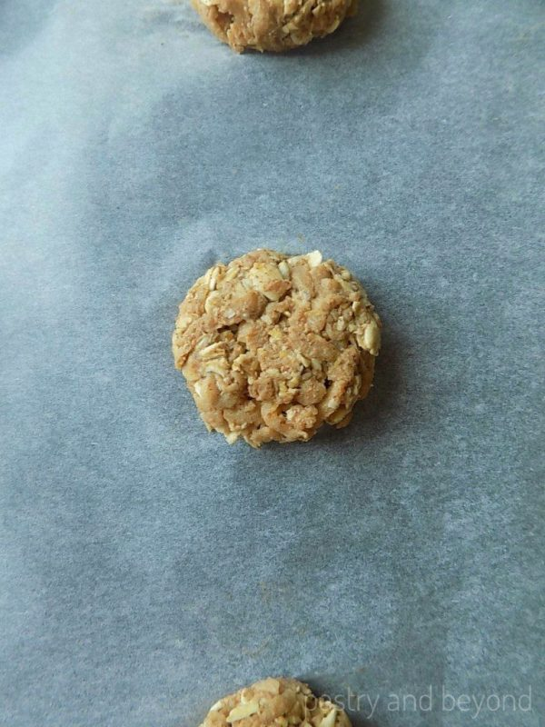 Step by Step Pictures of Healthy Apple Oatmeal Cookies: Rolled and flattened unbaked cookies on a baking sheet.