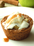 Apple crisp cookie cup topped with ice cream and syrup on a white plate.