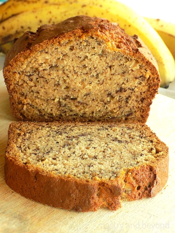 Banana Bread on a wooden board, bananas behind.