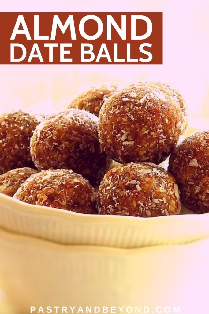 Almond date balls in a bowl on top of each other.