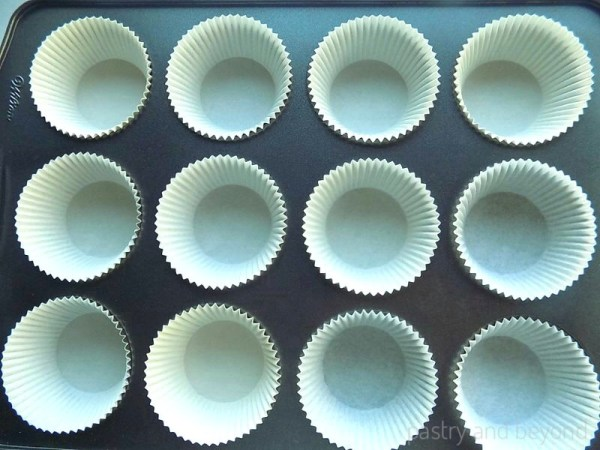 Cupcake liners placed in a 12 cup muffin tin.