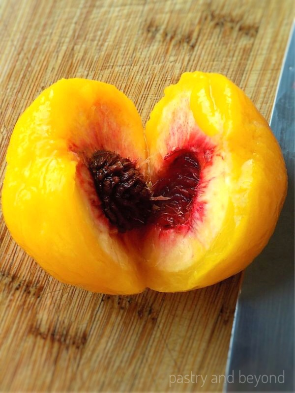 How to Pit Peaches step by step: Peach cut in half, pit in the middle