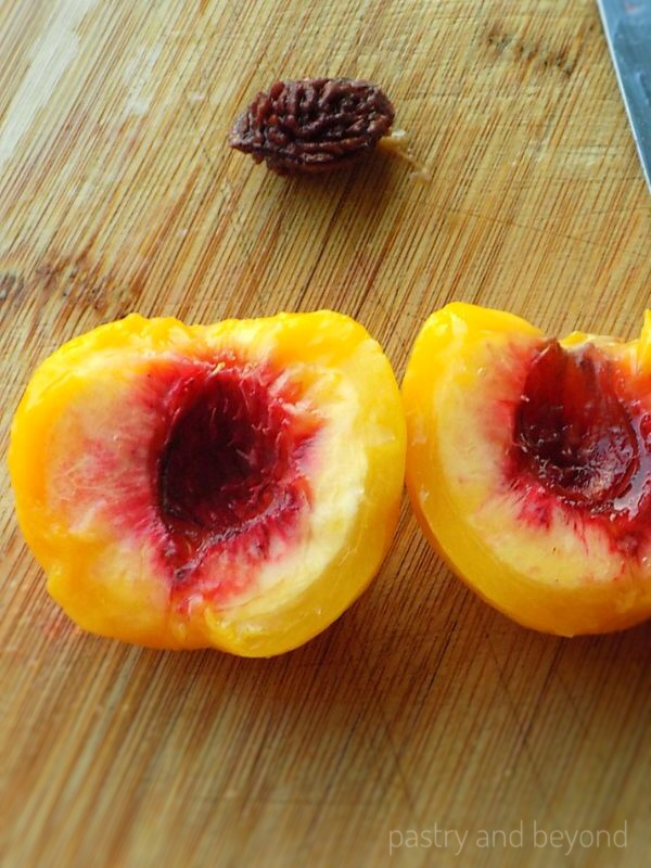 Halved peaches without pit, pit in the background.