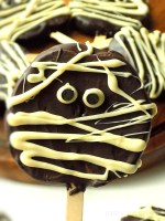 Chocolate covered apple slice on a wooden stick with a mummy design.