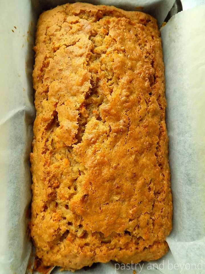 Carrot Cake in a loaf pan that is covered with parchment paper.
