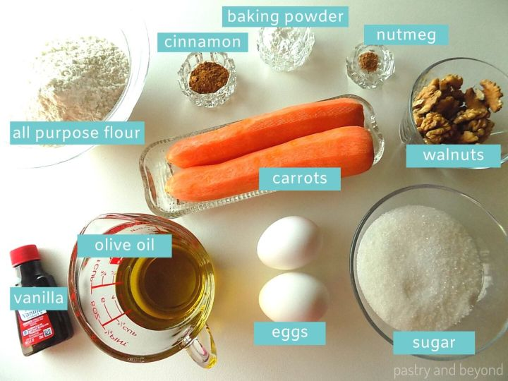 The Ingredients of a Carrot Cake Loaf on a white surface; vanilla extract, olive oil, eggs, sugar, carrots, walnuts, all purpose flour, cinnamon, nutmeg, baking powder