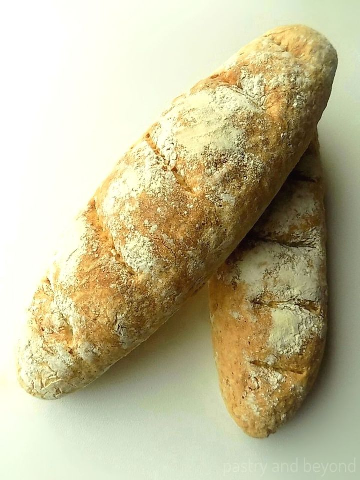 2 loaves of long bread on a white surface.