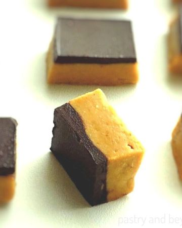 Side and overhead views of chocolate peanut butter no bake bars on a white surface.