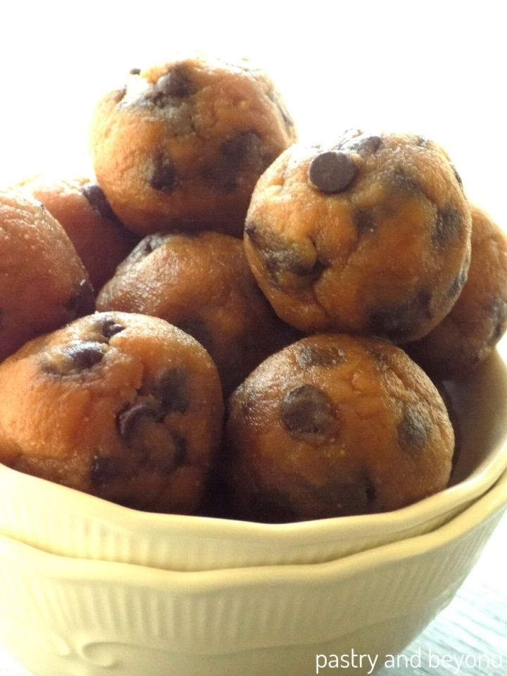 Peanut butter banana oat flour balls with chocolate chips randomly stacked in a white bowl.