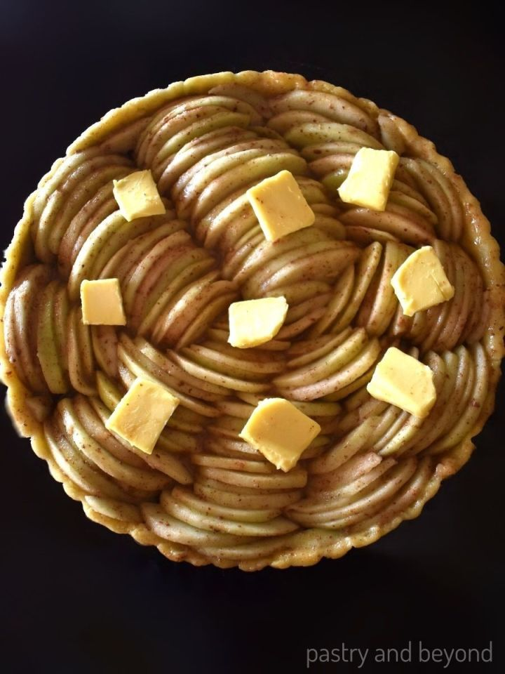 Apple slices with butter on top on unbaked tart crust in a pan.