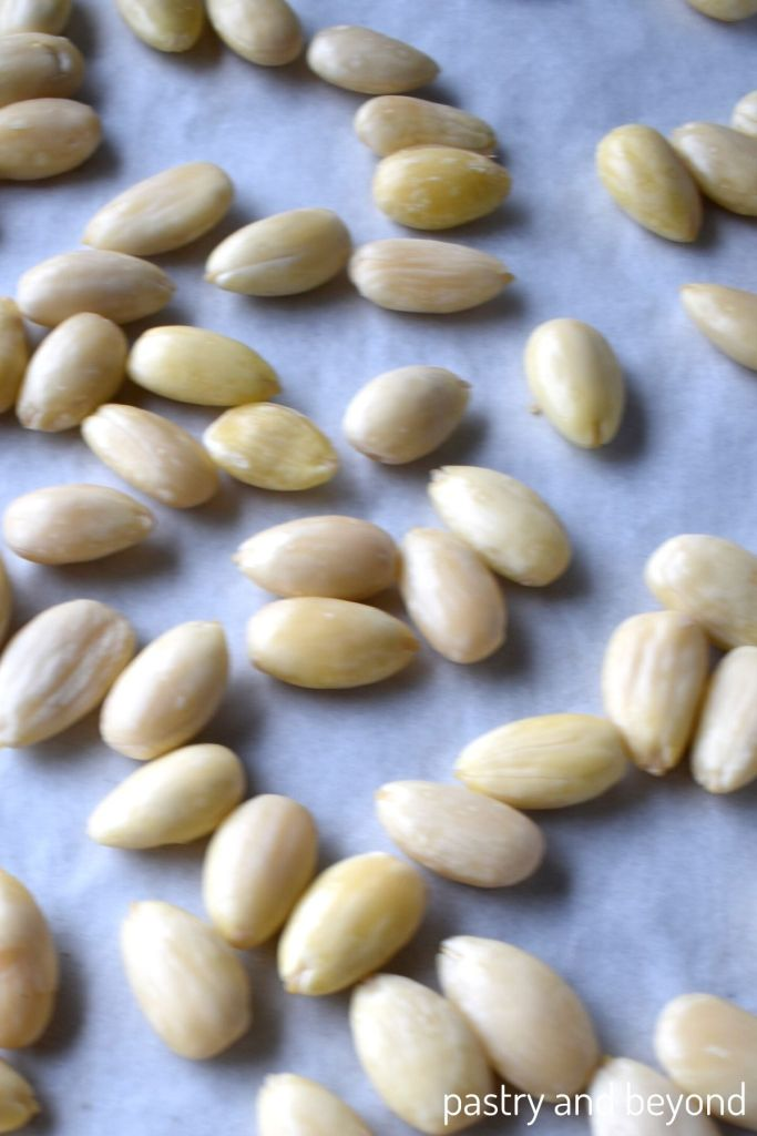 Blanched almonds on a parchment paper lined baking sheet.