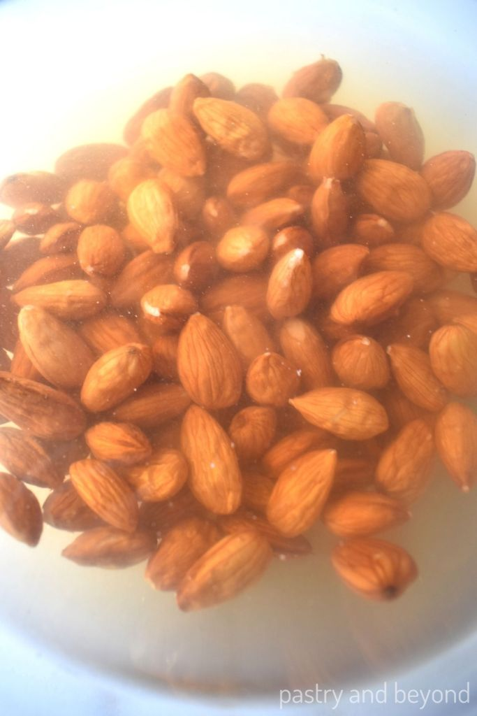 Raw almonds covered with water in a glass bowl to blanch the almonds.