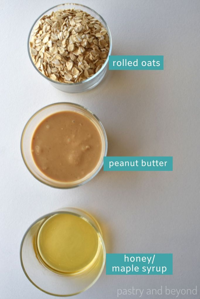 Ingredients for oatmeal balls in small cups on a white surface.