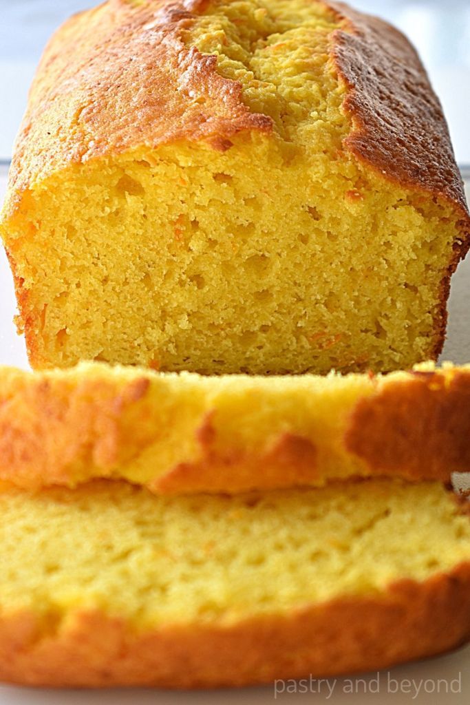 Orange cake loaf with slices on a white surface.