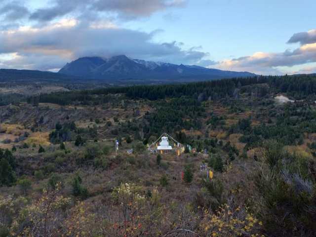 Panorámica de todo el sector donde está ubicada la estupa. Montañas de fondo y bosques rodeándola.