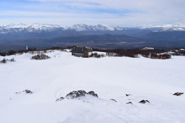 panorámica desde el Plateau. Se ve el refugio, árbboles y montañas en el fondo. Inauguración de la aerosilla en el Perito Moreno