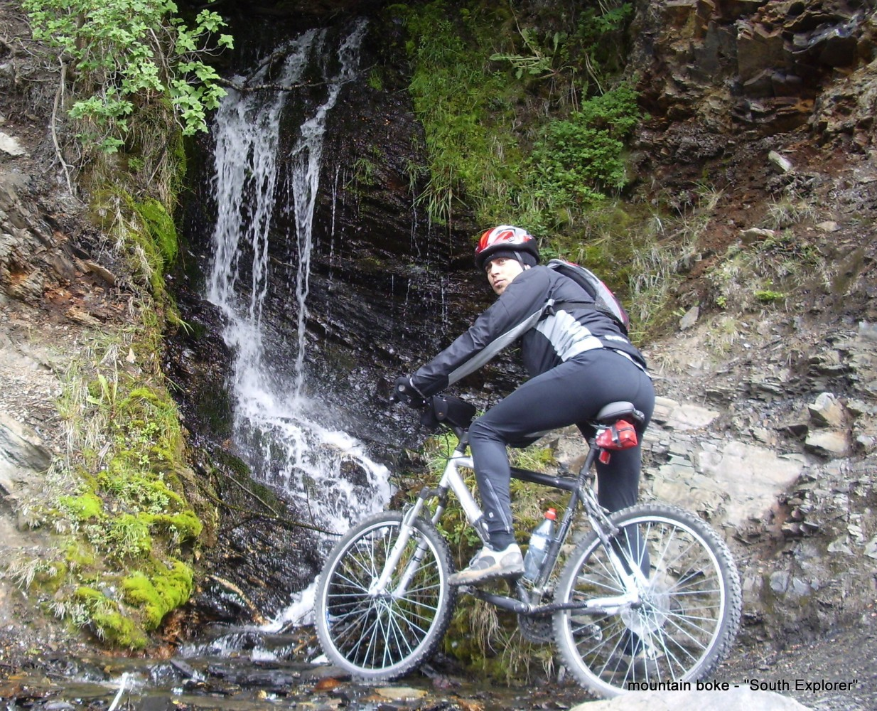 Hombre en bicicleta, mirando a cámara con una cascada detrás, paisajes que se ven en Tierra del Fuego en verano.