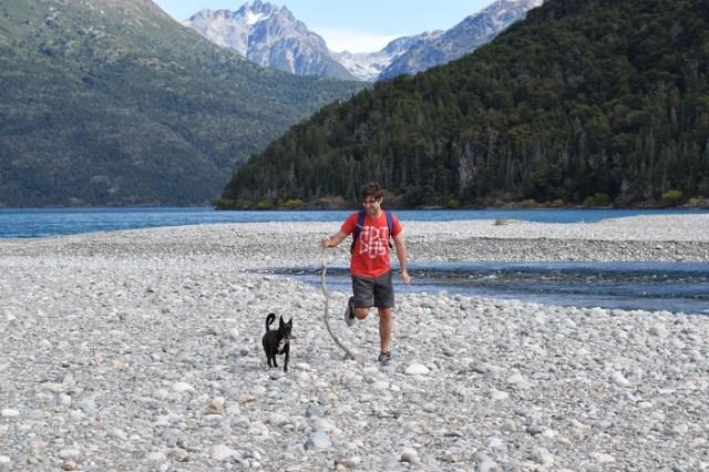 Hombre caminando con un perro. Los beneficios de hacer senderismo en la naturaleza.