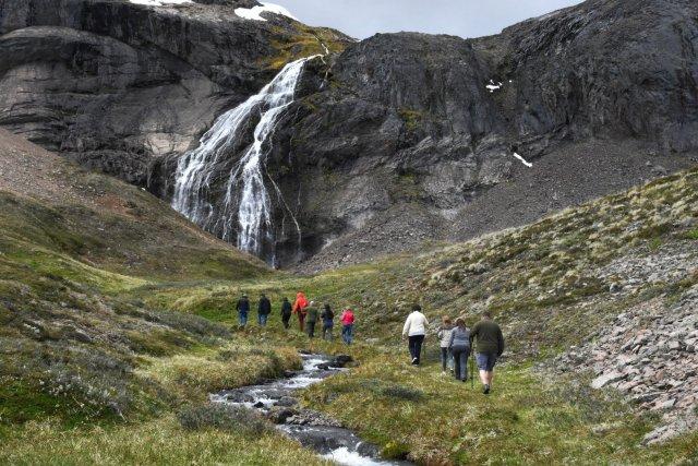 Grupo de personas con una cascada de fondo haciendo el sendero hacia el túnel.