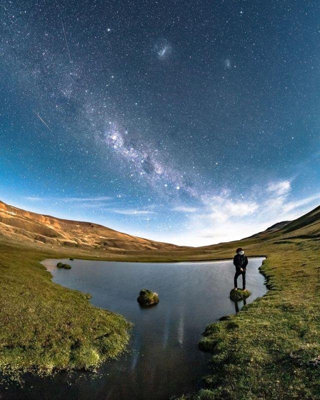 Hombre parado mirando el cielo realizando la experiencia nocturna en El Calafate.