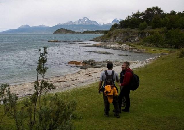Dos personas mirando hacia el lago dentro del Parque Nacional Tierra del Fuego. Una de las opciones para hacer trekking en verano.