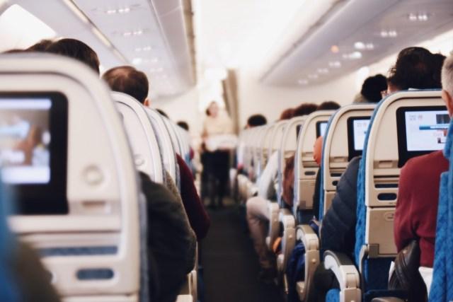 Parte de adentro de un avión con pasajeros.