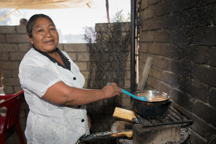 Maximina Morales Morales cooks food on an open fire at her roadside stand in Zaachila, outside of Oaxaca.