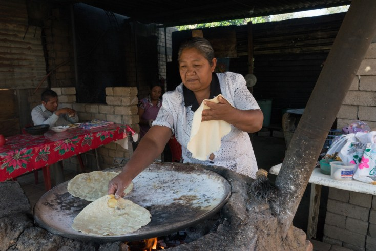 Maximina Morales Morales, in her roadside stand in Zaachila, a small town south of Oaxaca, makes tortillas using a comal and wood fire.