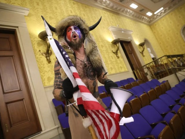 """A protester screams """"Freedom"""" inside the Senate chamber after the U.S. Capitol was breached by a mob during a joint session of Congress on January 06, 2021 in Washington."""