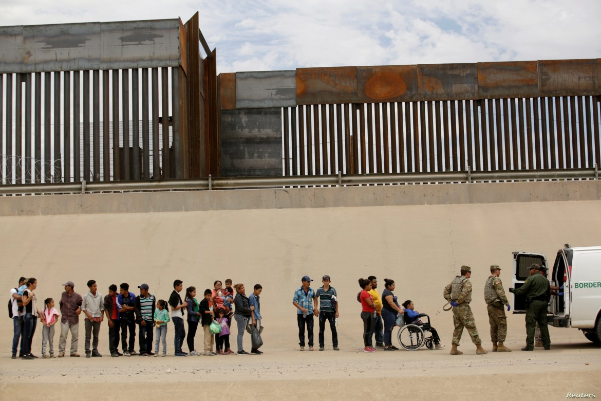 FILE - Members of the Border Patrol and U.S. military talk with migrants who illegally crossed the border between Mexico and the U.S. to request political asylum, as seen from Ciudad Juarez, Mexico, July 6, 2019.