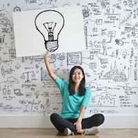 woman draw a light bulb in white board