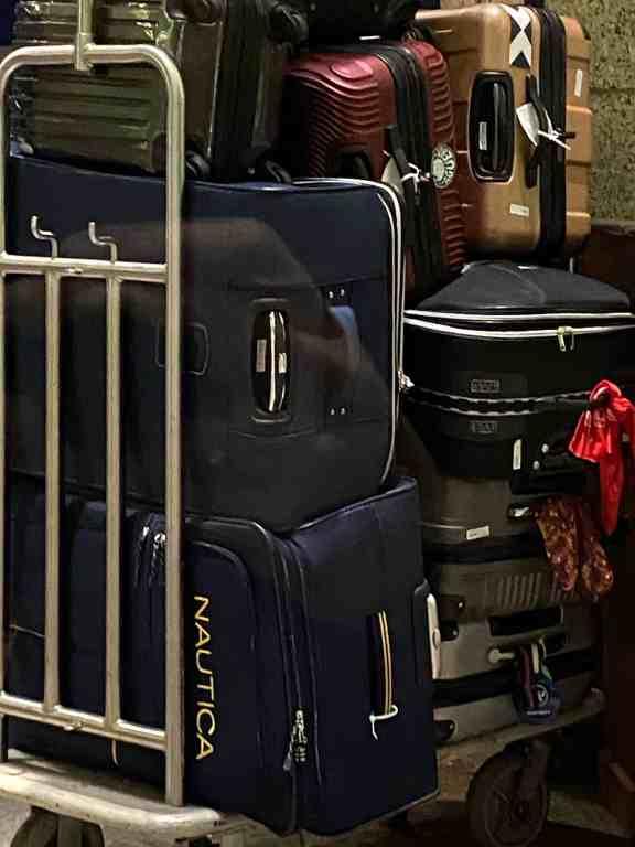 Foto mostrando uma pilha de malas no carrinho do hotel.