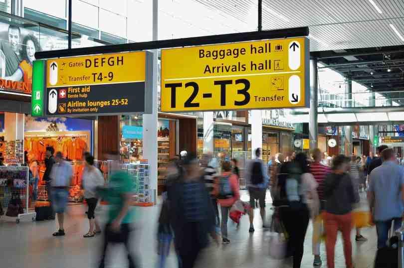 Imagem de aeroporto com sinalizaçÕes e pessoas passando.